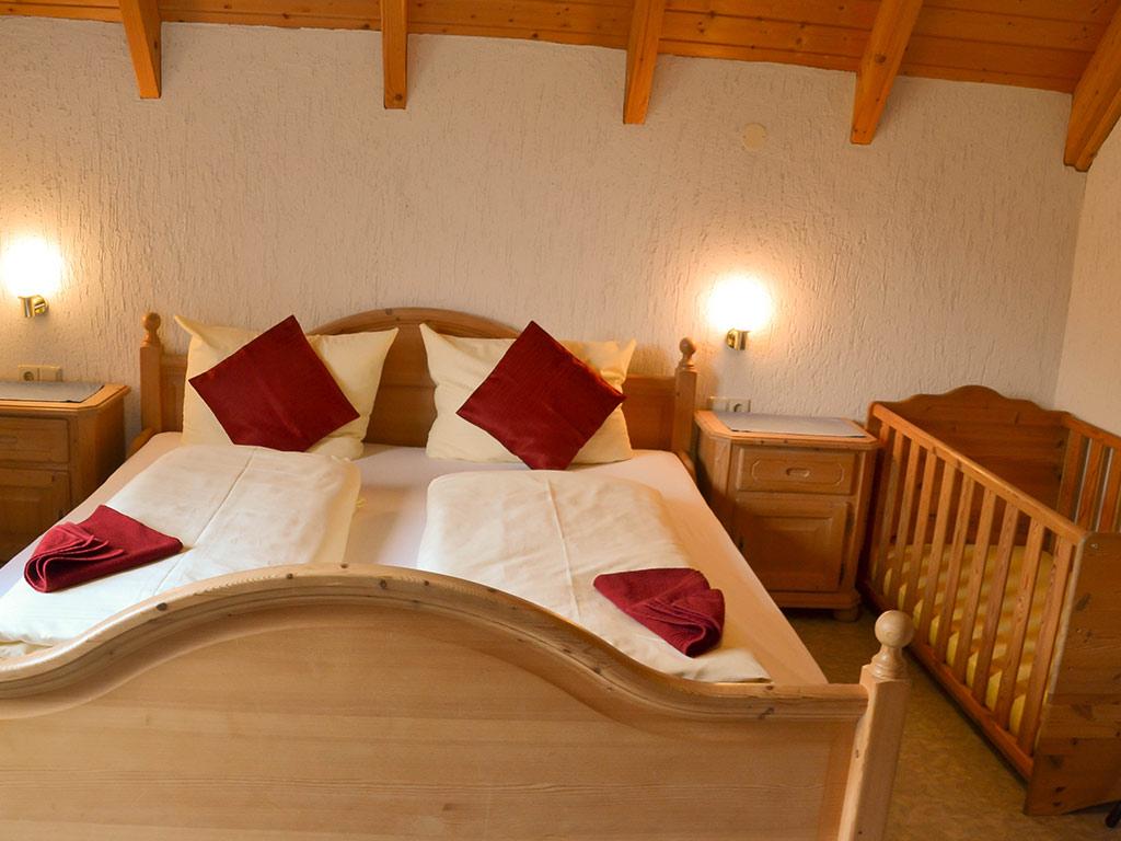 Ferienhaus Amsel, Ferienhof Jobs in Gerolfingen, Doppelbett mit Kinderbett